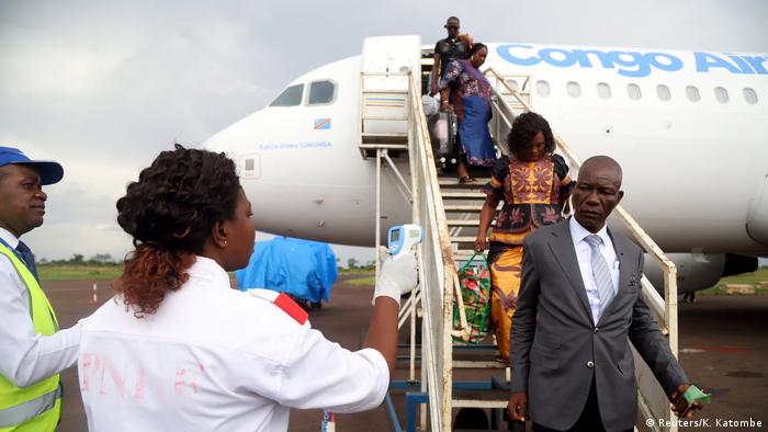 Passengers disembarking from a plane are met by health workers who will check their temperature
