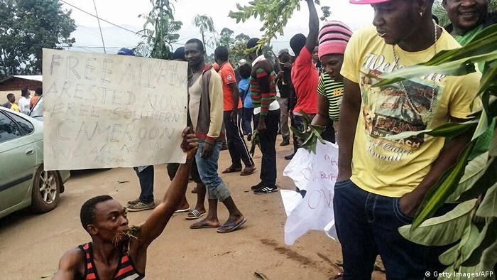 A demonstrator carries a banner calling for the freedom of detained English-speaking activists during a protest against discrimination in majority French-speaking Cameroon.
