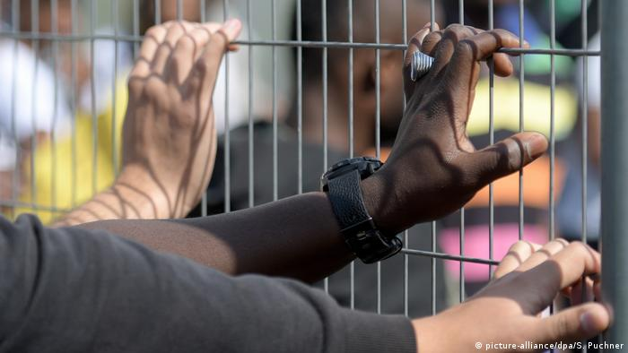 Drei Hände an einem Gitterzaun (picture-alliance/dpa/S. Puchner)