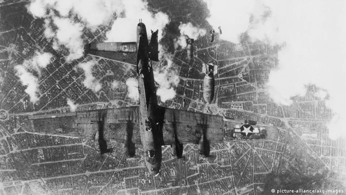 A plane flies above a city