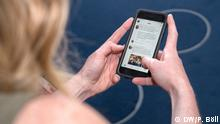 A woman uses a smartphone to check Twitter (DW/P. Böll)