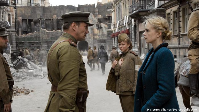film still shows woman with Russian soldiers from Anonyma - Eine Frau in Berlin