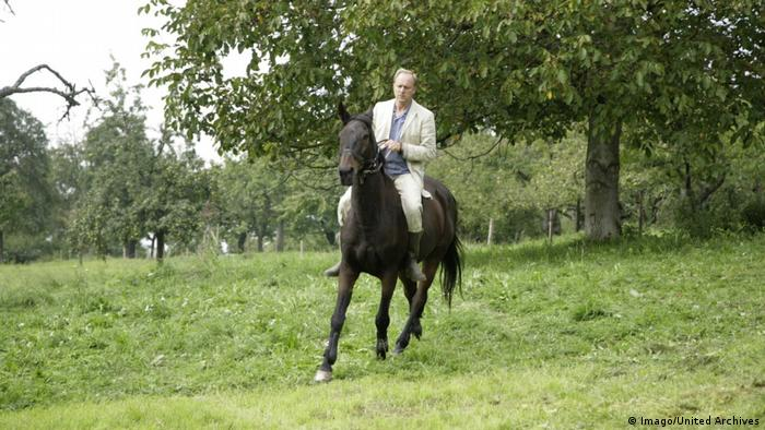 A man in a suit rides a horse over a grassy hill