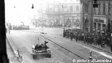 ARCHIV - Teilnehmer der Massendemonstration, die zu dem Aufstand führte, gehen am 23.10.1956 passieren in der Innenstadt von Budapest einen sowjetischen Panzer. Im Hintergrund liegt der Torso, des von der Menge gestürzten Stalindenkmals auf der Straße. Foto: dpa (zu dpa «Doku von Leslie Mandoki über ungarischen Volksaufstand» vom 21.10.2016 - nur s/w) +++(c) dpa - Bildfunk+++ | 100 Must-Reads Zsuzsa Bánk Der Schwimmer