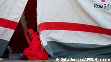 A migrant keeps warm inside a Red Cross tent upon his arrival at Malaga's harbour on April 26, 2018