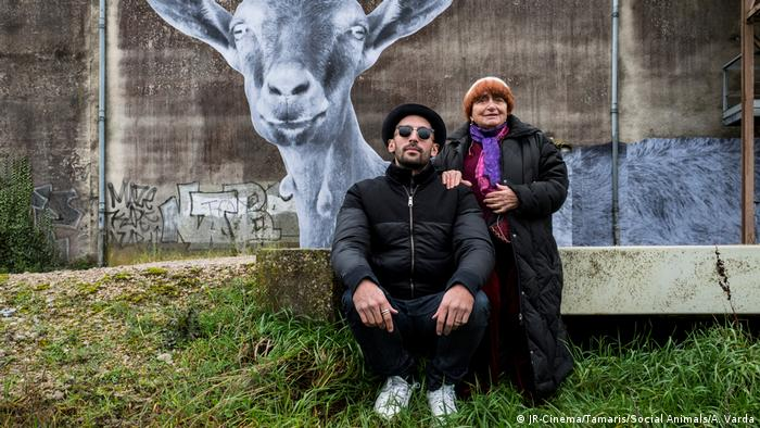 Artist JR and director Agnes Varda sitting on a bench in front of a concrete wall (JR-Cinema/Tamaris/Social Animals/A. Varda)