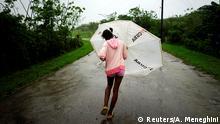REFILE - CORRECTING GRAMMAR Dalma Samora, 14, walks against the winds of Subtropical Storm Alberto as it passes by the west coast of Cuba, in La Palma, Cuba, May 26, 2018. REUTERS/Alexandre Meneghini