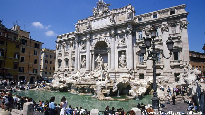 Fontana di Trevi em um dia de sol, com muitos turistas em seu entorno.