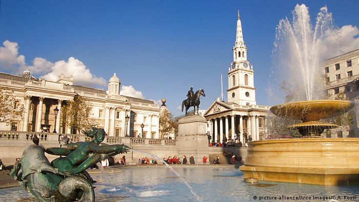 Grande chafariz jorra água, com igreja e estátua ao fundo.