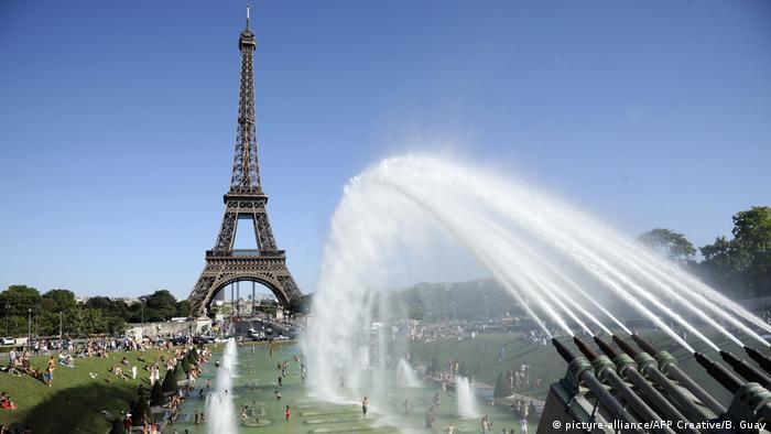 Em um dia de sol e com céu sem nuvens, canhões disparam água em direção à Torre Eiffel.