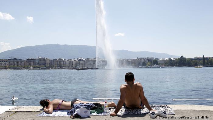 Mulher de biquini toma banho de sol às margens do rio e homem observa o grande jato de água.