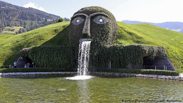 Fonte em forma de rosto, com olhos de brilhantes e água jorrando pela boca.