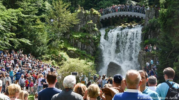 Muitos turistas observam queda de água no parque. Sobre a queda, há uma ponte, também repleta de turistas.