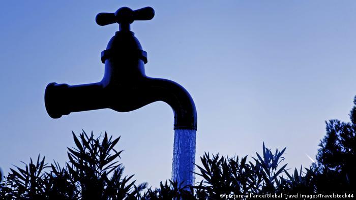 Grande torneira parece flutuar no ar, jorrando água.