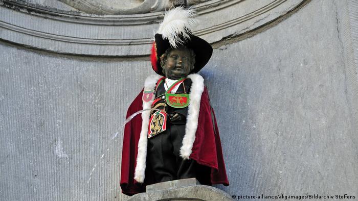 Manneken Pis vestido com capa vermelha e chapéu com plumas brancas.