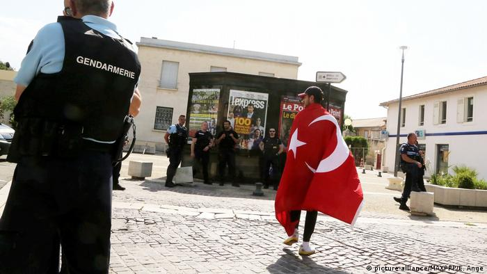 A man carrying a Turkish flag approaches police