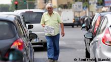 Italien Ein Mann läuft in Rom mit dem Schild Armer Italiener, eine Hilfe, Danke
