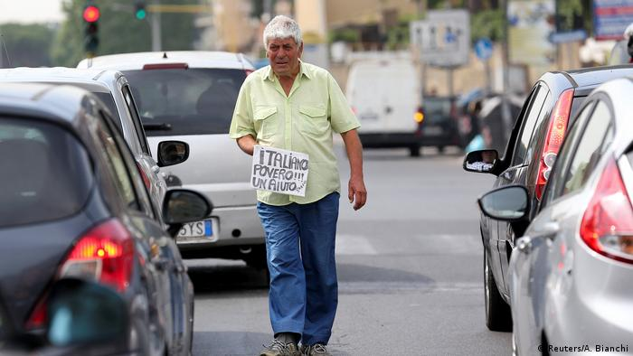 'Siromašan Talijan, molim pomoć, hvala' piše na papiru ovog muškarca na ulici Rima