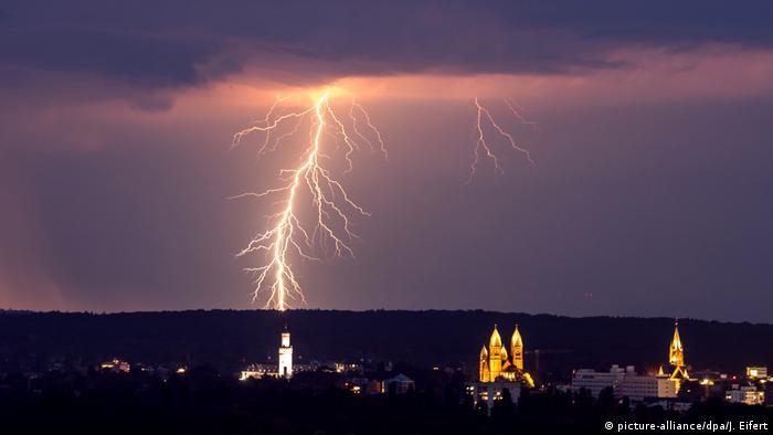 Über einer erleuchteten Stadt zuckt ein Blitz durch den Nachthimmel