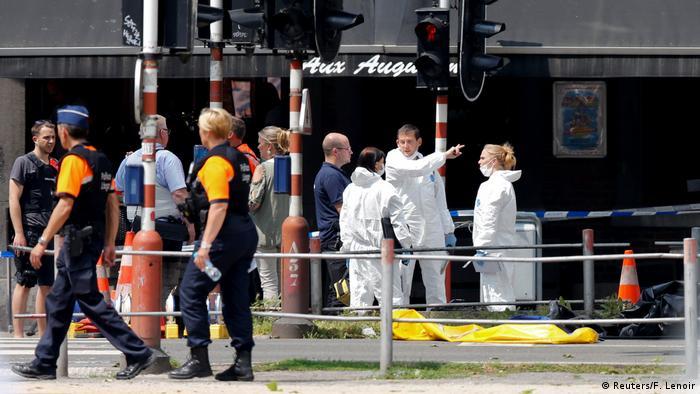 Especialistas forenses, vestidos de branco, conversam com um homem.