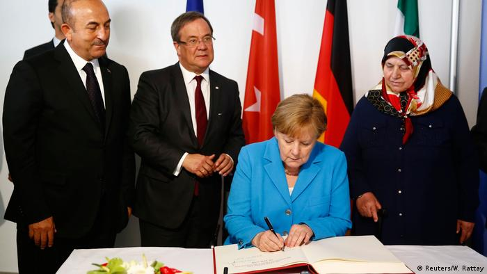 Angela Merkel signs a memorial book at the conmemoration of the Solingen attacks in Düsseldorf