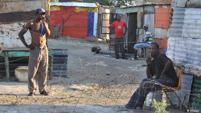 Jobless black South Africans standing and sitting in front of shacks in a township (Imago)