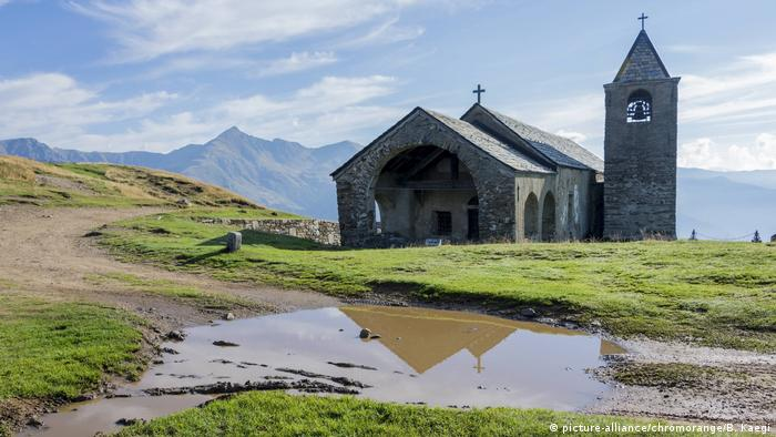 Chweiz Romanische Wallfahrtskirche San Lucio im Vordergrund