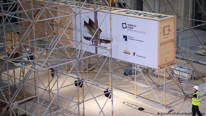 Large crate balancing among scaffolding