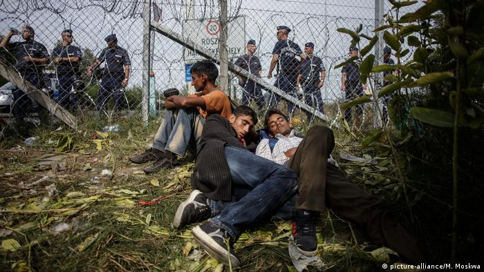 Refugees sit against a fence in Hungary. Police line the other side of the fence (picture-alliance/M. Moskwa)