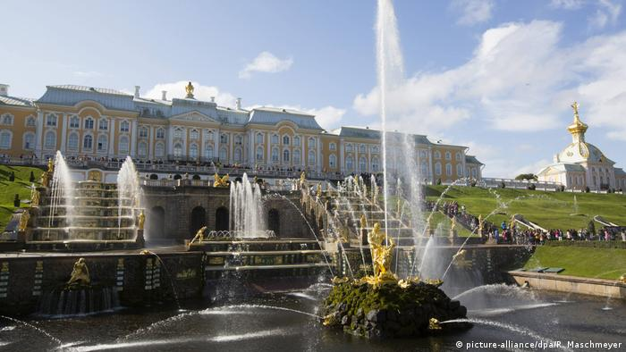 Em um dia de sol, chavarizes jorram água, com o palácio ao fundo.