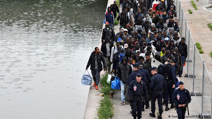 Migrants await by the side of the river Getty ImagesAFPG Julien