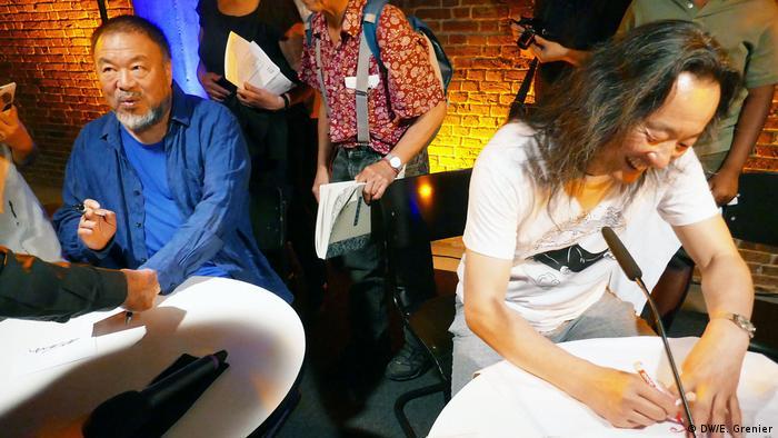 Ai Weiwei und Yang Lian signieren Bücher und T-Shirts bei der Lesung Elegie und Aufbruch beim 19. Poesiefestival Berlin. (DW/E. Grenier)