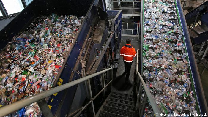 A worker walks past mounds of bottles at a PET recycling plant