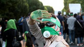 Supporter of Mousavi, covers her face with piece of cloth in green and a sign in Persian reads Mir Hossein Mousavi during a rally in Tehran