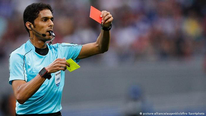 Referee Fahad Al Mirdasi with red and yellow cards in his hands (picture-alliance/augenklick/firo Sportphoto)