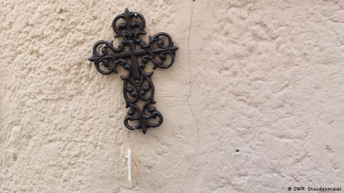 A cross hangs on a wall outside of a shop in Passau (DW/R. Staudenmaier)