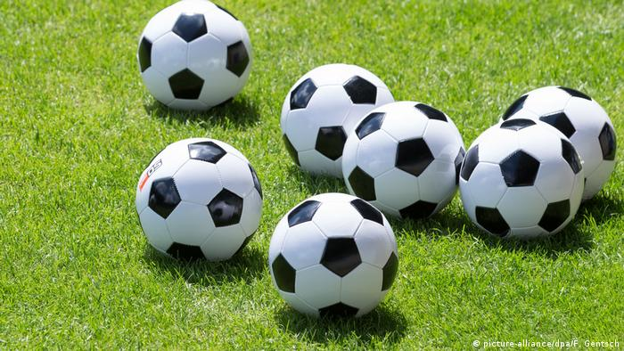 Several soccer balls lying on a field (picture-alliance/dpa/F. Gentsch)