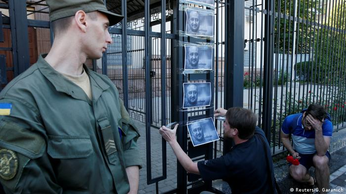 A man hangs a picture of Arkady Babchenko on a fence of the Russian embassy in Kyiv on May 29, when he was still believed dead (Reuters/G. Garanich)