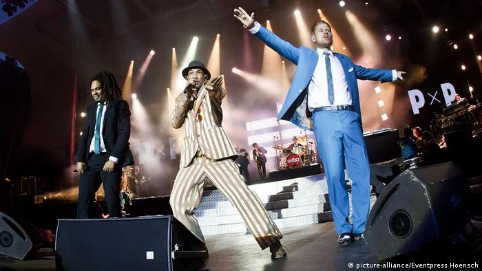three men leap on stage in colorful suits (picture-alliance/Eventpress Hoensch)