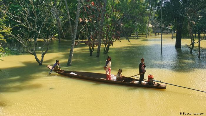 Children of Kbal Romeas in a canoe in the flooded forest