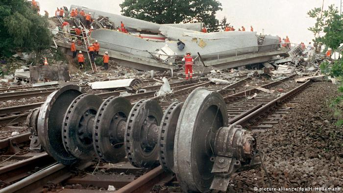 A detached wagon axle. In the background emergency workers climbing onto broken wagons (picture-alliance/dpa/H. Hollemann)