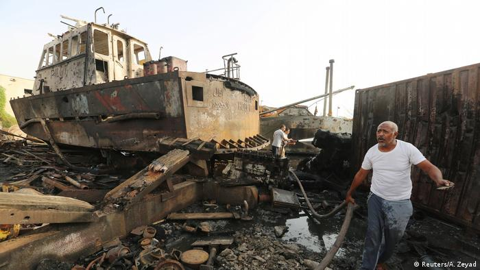 Workers inspect the bombed out remains of a boat at a maintenance hub at the port of Hodeida.