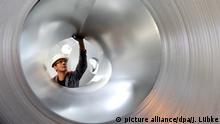 ARCHIV - Ein Mitarbeiter der Salzgitter AG begutachtet im Stahlwerk in Salzgitter ein Coil (Archivfoto vom 15.09.2010). Am Freitag findet in Düsseldorf eine Pressekonferenz der Wirtschaftsvereinigung Stahl mit Präsident Hans Jürgen Kerkhoff statt. Thema sind die Konjunkturprognose für die Stahlindustrie 2016 sowie um die Einschätzung der Auswirkungen des Pariser Klimagipfels auf die deutsche Branche Foto: Jochen Lübke/ dpa +++(c) dpa - Bildfunk+++ | Verwendung weltweit