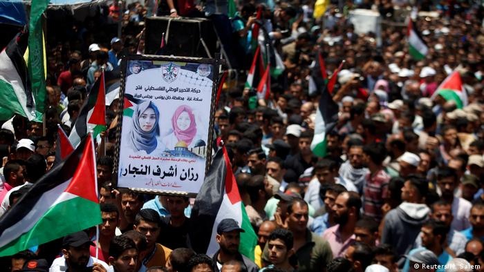 Mourners attend the funeral of Palestinian nurse Razan Al-Najar, who according to health officials and a witness was killed by Israeli forces as she tried to help a wounded protester at the Gaza border