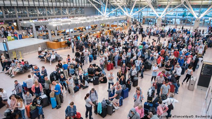 Passengers wait in lines at Hamburg Airport after operating systems went back online following a blackout