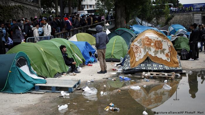 Migrants wait to leave during a clearing out of a makeshift migrant camp along side of the canal Saint Martin, in central Paris