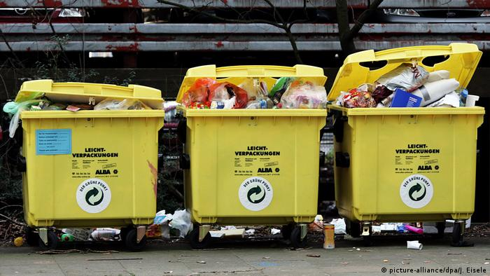 Three yellow bins overflowing with plastic waste