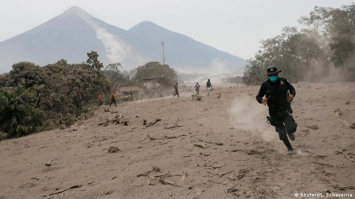 A policeman runs away from the volcano in Guatemala (Reuters/L. Echeverria)