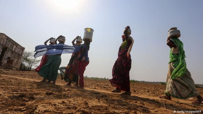 Indian women return to their village after fetching