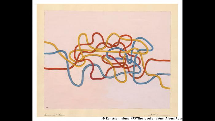 Blaue, rote und gelbe gemalte Fäden durcheinandergewuselt